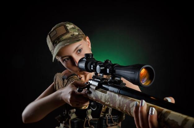 Сексуальная девушка в военном комбинезоне для страйкбола позирует со снайперской винтовкой на темном фоне