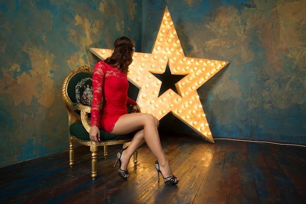 고급스러운 빨간 드레스와 하이힐에 붉은 입술을 가진 섹시한 여자가 금색과 밝은 별이있는 풍부한 스튜디오 인테리어에 의자에 앉아있다.