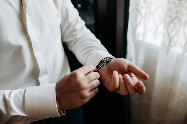 섹시한 남성 사업가가 고급스러운 흰색 셔츠 소매 커프를 자신의 손목 시계에 커프스 단추로 고정시킵니다.