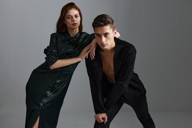 Сексуальный мужчина в костюме наклонился вперед, а привлекательная женщина в вечернем платье. фото высокого качества