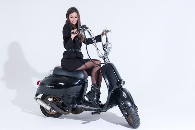 セクシーな女性がバイクに座っています。黒のドーベルマンが愛人を守る