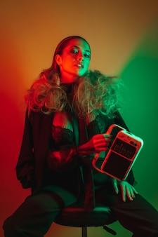 ラジオプレーヤーを保持している黒い透明なシャツを着たセクシーな若いブロンドの髪の女性