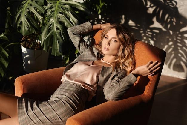 ビジネススーツのセクシーな若い女性は、彼女の後ろの壁に植物からの影が付いているオフィスの肘掛け椅子にかかっています。シャドウオーバーレイ効果。市松模様のスーツのモデルの女の子が肘掛け椅子に座っています。