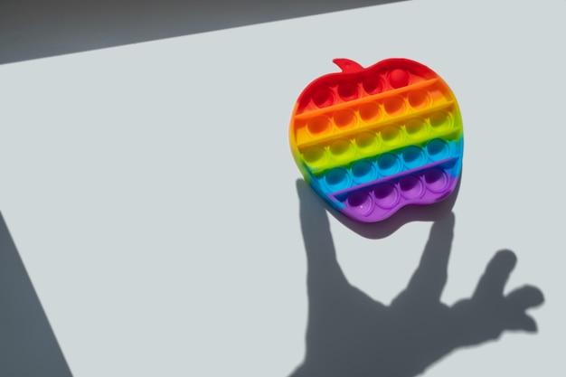 手の形をした影がシリコンおもちゃのアンチストレスを保持し、シンプルなディンプルをポップします。子供向けの新しいトレンドフィジェットdof