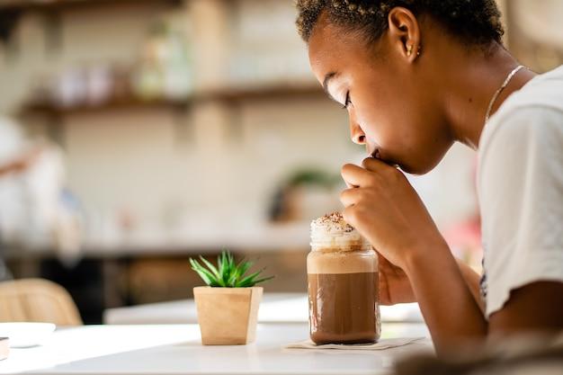 밀크 쉐이크를 마시는 아프리카 계 미국인 여성의 얕은 초점 샷
