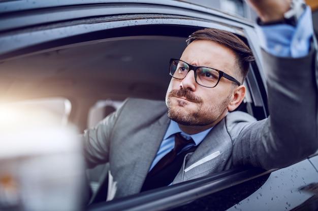 예리한 옷을 입은 남자는 자신이 출퇴근 시간에 걸리고 천천히 도로 분노에 굴복했습니다.