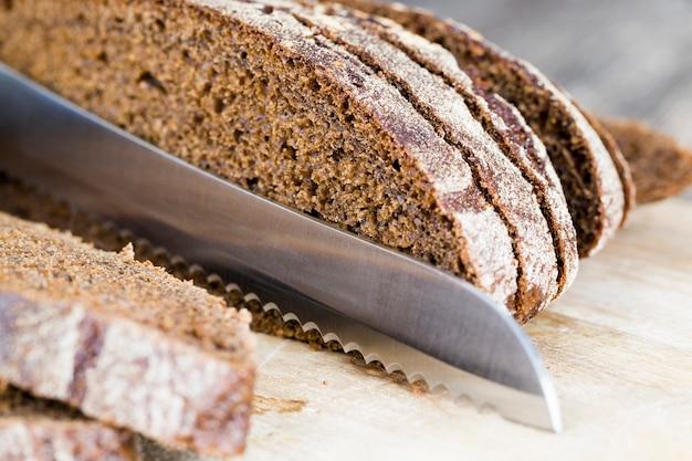 鋭い金属製のナイフと香りのよいライ麦パンの柔らかいパン、小麦粉からスライスした食品のクローズアップ