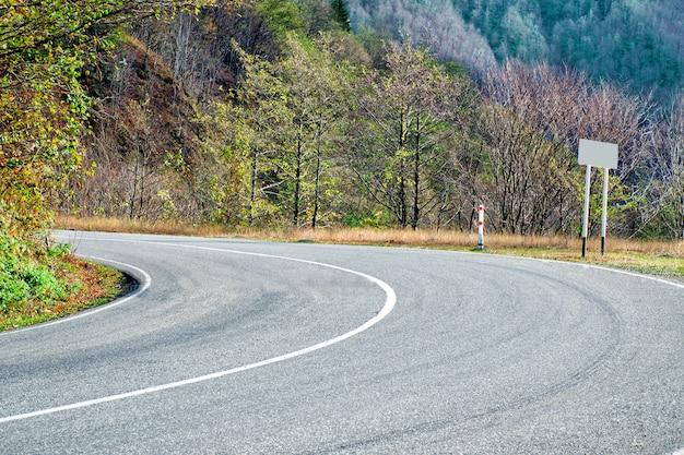 Резкий поворот на дороге между зелеными деревьями и горами.