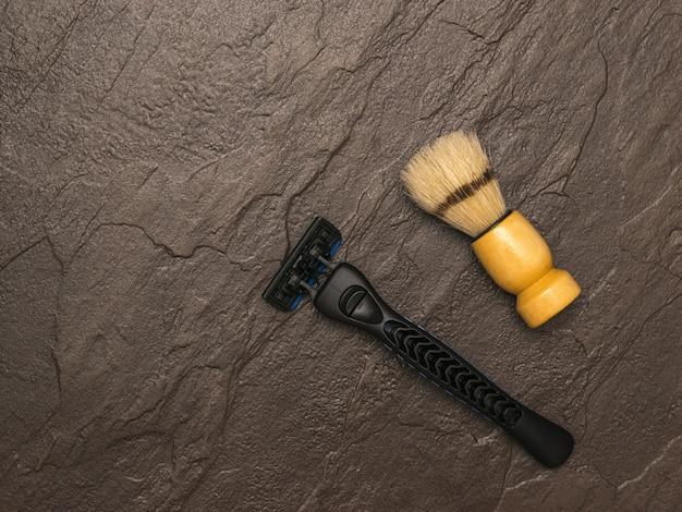 木製のハンドルと石の背景に青いかみそりが付いたシェービングブラシ。男の顔のケアのために設定します。フラットレイ。