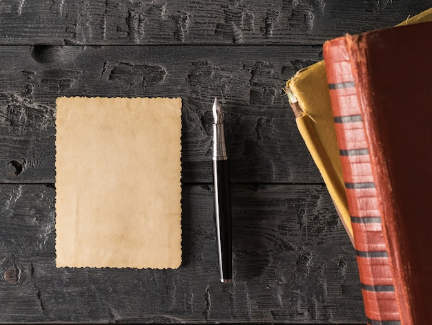 Лист старой бумаги и перьевая ручка с книгами на деревянном столе. ретро писчая бумага. плоская планировка вид сверху.