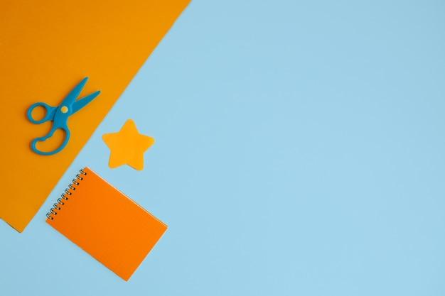 はさみ、オレンジ色のメモ帳、青い背景に星型のステッカーが付いたオレンジ色の紙のシート。コピースペースのあるフラットレイアウト