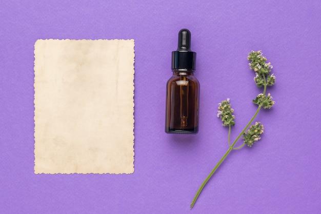 Лист бумаги, флакон с лекарством и лекарственное растение на фиолетовом фоне. концепция лечения и ухода за телом с помощью натуральных средств. плоская планировка.