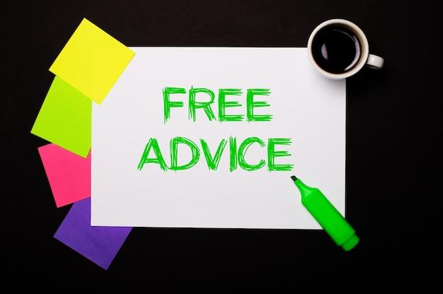 Free adviceという言葉が書かれた一枚の紙、一杯のコーヒー、メモ用の明るいマルチカラーステッカー、黒い表面に緑色のマーカー