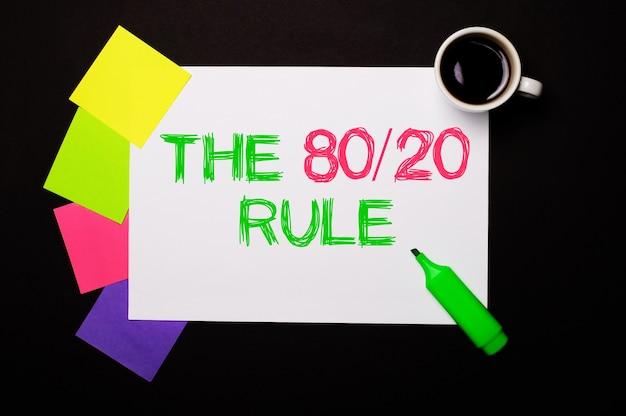 80 20 룰이라는 단어가 적힌 종이, 커피 한 잔, 밝은 색의 메모 용 스티커, 검은 색 표면에 녹색 마커. 위에서 봅니다.