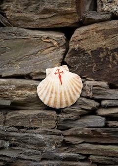 Ракушка с нарисованным красным крестом, символом пути сантьяго, на вершине нескольких камней.