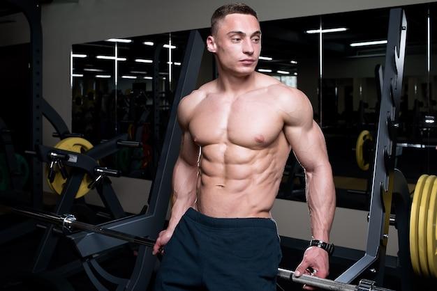 体育館のバーベルに、肌の色が薄い上半身裸の細断ボディービルダーが座っています。