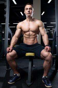 薄い肌の上半身裸の細断されたボディービルダーはベンチに座っており、彼の手はジムで膝の上に横たわっています