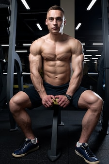 肌の色が薄い上半身裸の細断されたボディービルダーがベンチに座って、ジムで胸筋を圧迫しています。