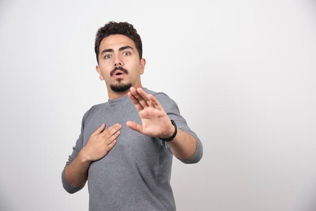 흰 벽에 손으로 포즈 충격 된 남자.