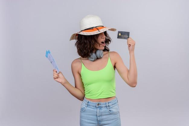 白い背景の上のクレジットカードを見て飛行機のチケットを保持している太陽の帽子をかぶってヘッドフォンで緑のクロップトップの短い髪のショックを受けた若い女性