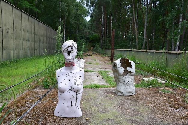 Тир в лесу с обстрелянными мишенями - манекенами.