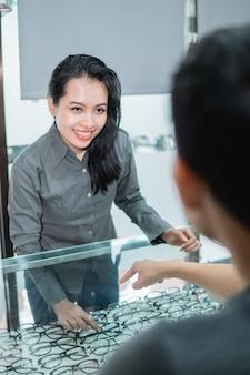 Продавец показывает пару очков в витрине покупателю в оптике.