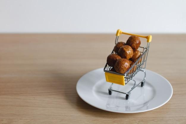Корзина из супермаркета заполнена фрикадельками. концепция покупки еды