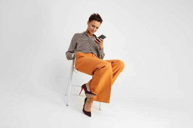 Стриженная девушка в брюках и рубашке сидит на стуле и читает сообщения по телефону на белом