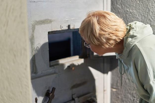 短い髪の女性が独房のドアの窓の外を見ています。刑務所の警備員が独房で秩序を保つ