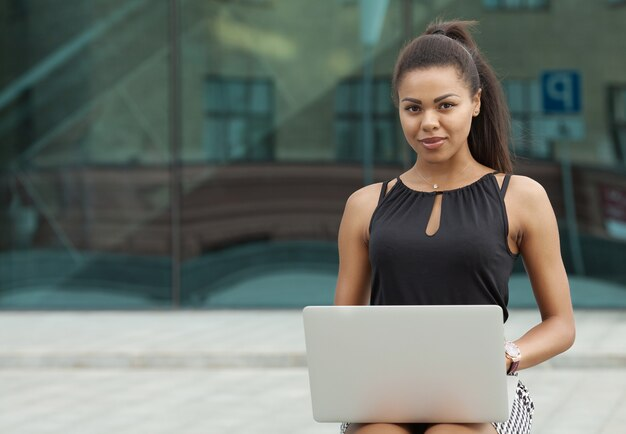 屋外で彼女のラップトップに取り組んでいる黒の実業家のショット