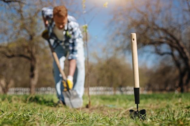 봄에 정원을 가꾸는 성숙한 남자의 샷, 새 나무를 심고 앞에 땅을 파는 국자