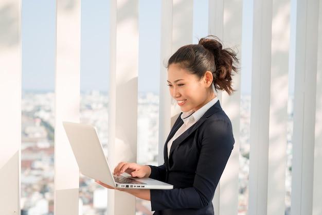 Выстрел бизнес-леди, работающей на своем ноутбуке на открытом воздухе