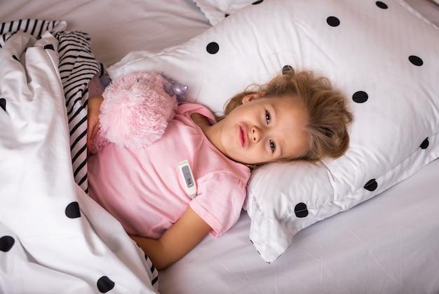 아픈 아이가 부드러운 장난감을 가지고 침대에 누워 온도계로 온도를 측정합니다