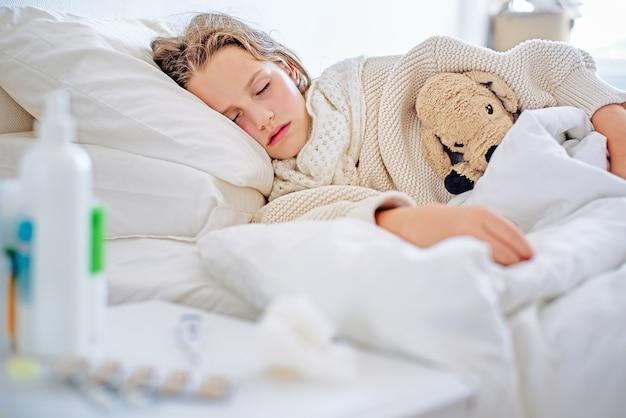 온도가 높은 아픈 소녀가 침대에서 자고 있습니다.