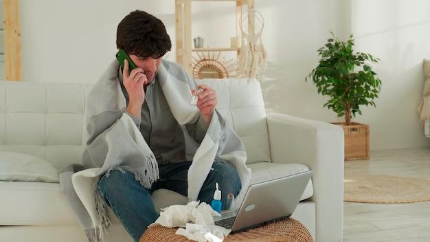 아픈 남자가 전화로 의사에게 전화를 겁니다. 남자가 아프고 집에서 소파에 앉아 있습니다.