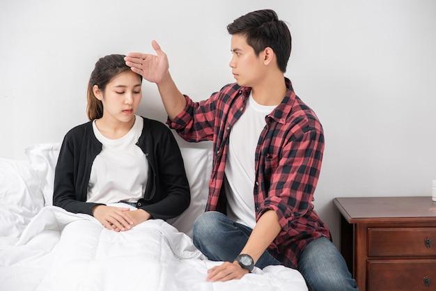 病気の女性は男性に顔を見せ、額に触れさせた。