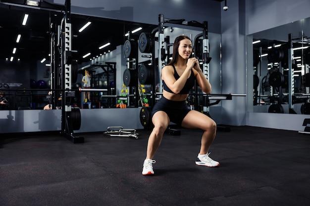 스포츠 브래지어와 반바지에 웃는 소녀의 측면 프로필보기는 어두운 실내 체육관에서 교차 한 팔로 깊은 윗몸 일으키기를합니다. 사랑 스포츠, 도전