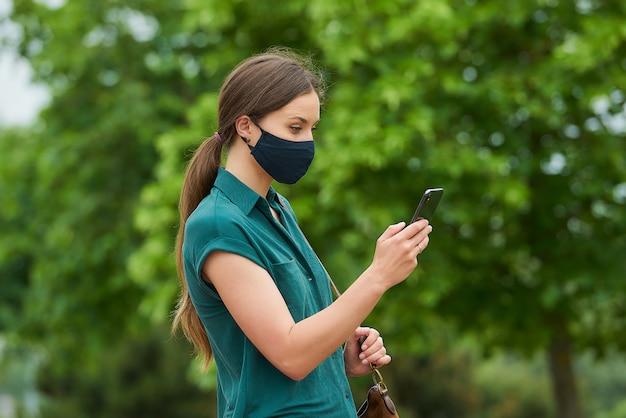 의료 얼굴 마스크에 젊은 여자의 측면보기는 스마트 폰에서 뉴스를 읽고 공원에서 산책하는 동안 가방을 들고있다