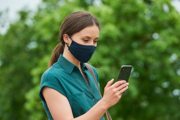 의료 얼굴 마스크에 젊은 여자의 측면보기는 공원에서 산책하는 동안 스마트 폰 뉴스를 읽고있다