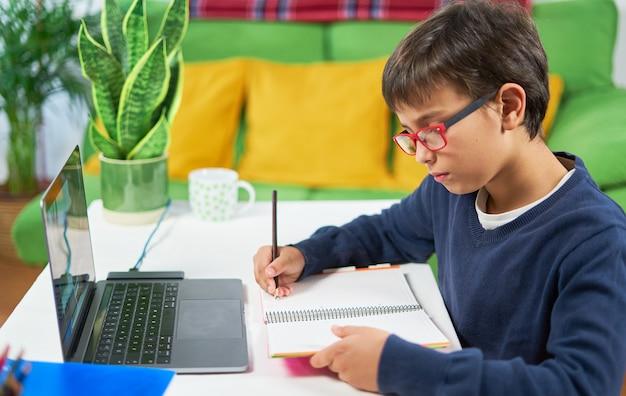 Вид сбоку на готового к школе мальчика с онлайн-классами, сидя дома в карантине,