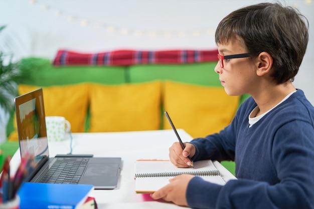 격리 된 집에 앉아있는 동안 온라인 수업과 함께 학교 준비 소년의 측면보기,