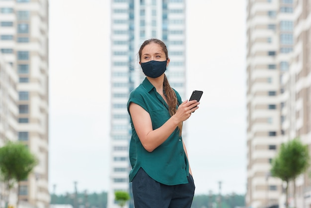 의료 얼굴 마스크에 여자의 측면보기는 바지의 주머니에 손을 밀어 스마트 폰 뉴스를 읽습니다 고층 빌딩 사이 산책