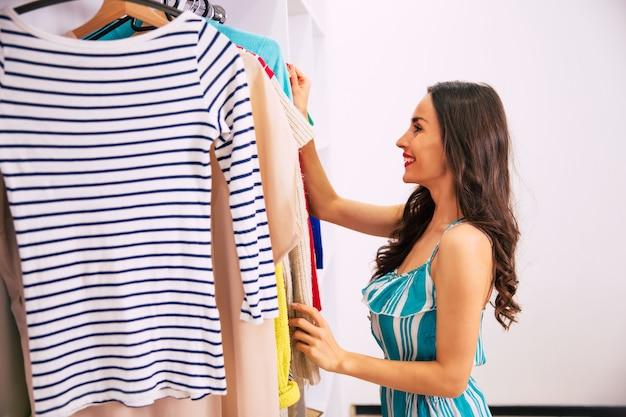 옷에서 입을 옷을 찾고 있는 줄무늬 드레스를 입은 아름다운 소녀의 측면 사진이 옷장에 매달려 있습니다.