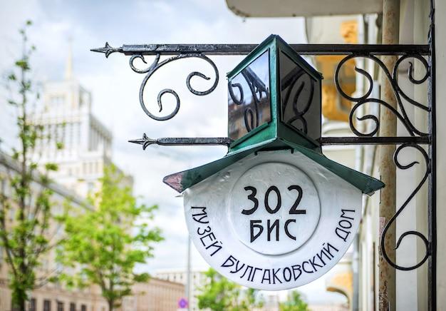 Вывеска у музея булгакова в москве в солнечный летний день. надпись: 302 bis, дом-музей булгакова.