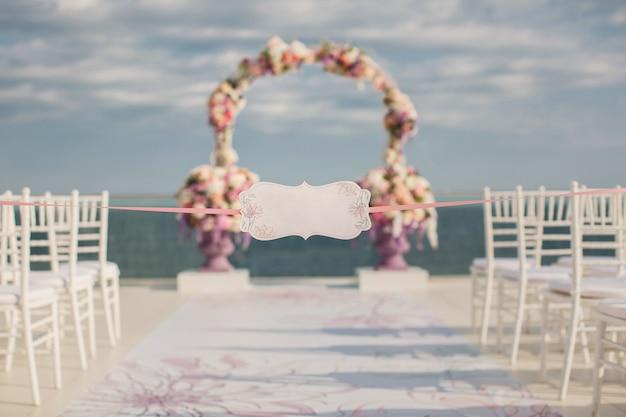 結婚式のアーチと海を背景にしたサイン。
