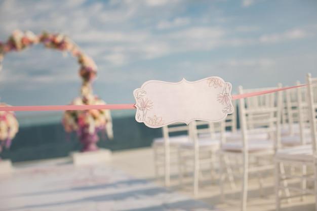 結婚式のアーチと海を背景にした看板。