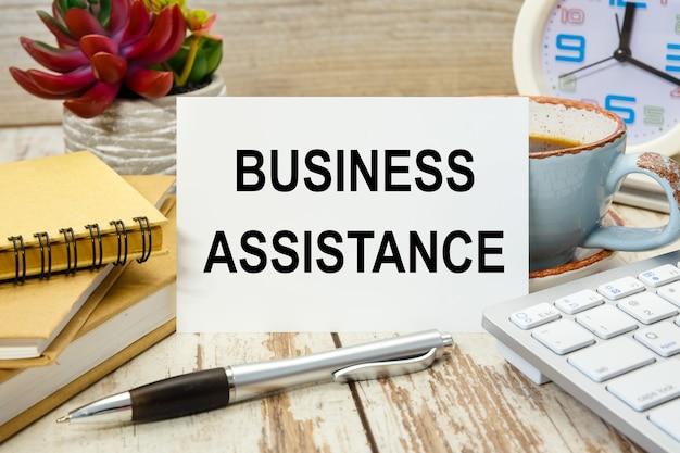 Табличка с надписью бизнес-помощь на столе с канцелярскими товарами