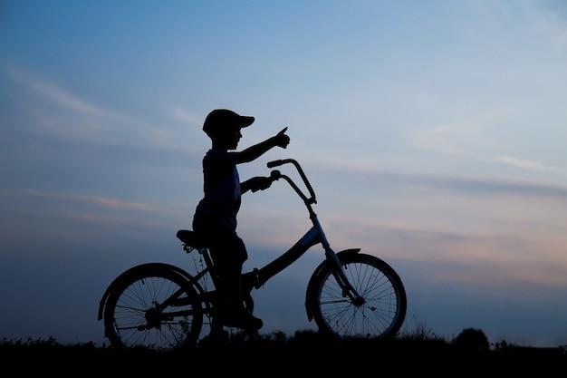 自然の中で自転車に乗っている少年のシルエット