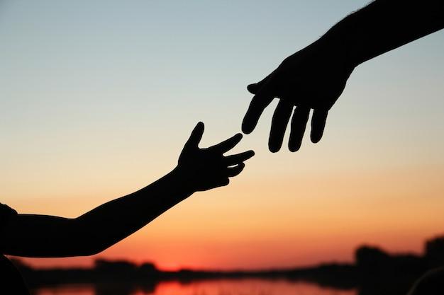 親のシルエットは小さな子供の手を握ります