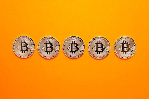 오렌지 벽에 가로 행에 실버 bitcoin 동전. 암호 화폐